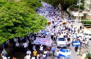 "På den handskrivna skylten står det ""From Honduras to the World, we don't want Zelaya back"""