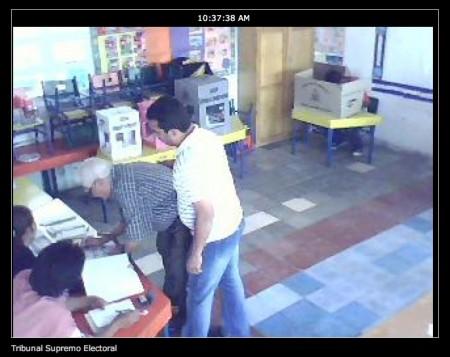 Äldre honduran får hjälp att rösta i Col. El Pedregal, observerad via internetkamera.